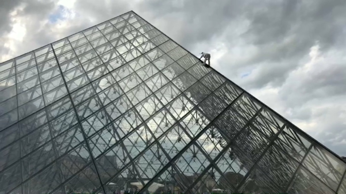 Vu à Paris : Un militant d'Extinction Rébellion escalade la pyramide du Louvre